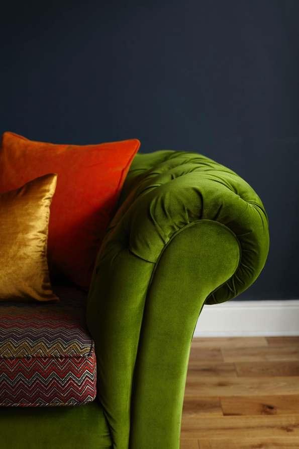 green velvet sofa, red, yellow pillows