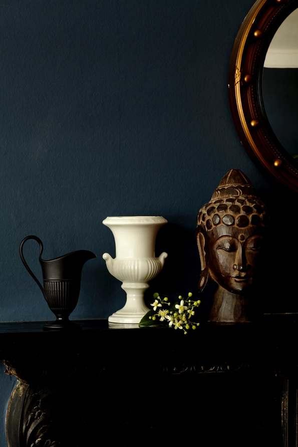still life: black urn, white vase, buddha head on mantel next to round mirror