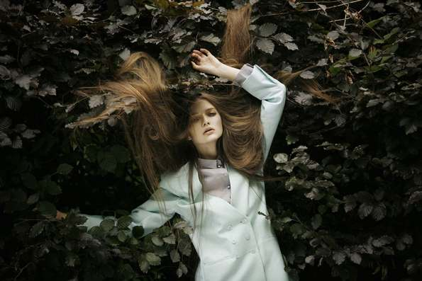 Fashion model with hair spread on leaves