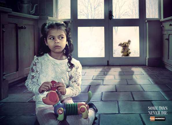 Young girl playing with toy while old toy watches from outside the door